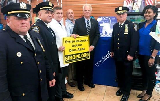 "DA Michael McMahon standing with NYPD holding The ""Staten Islanders Against Drug Abuse"" SIHOPE.org Lawn Sign"