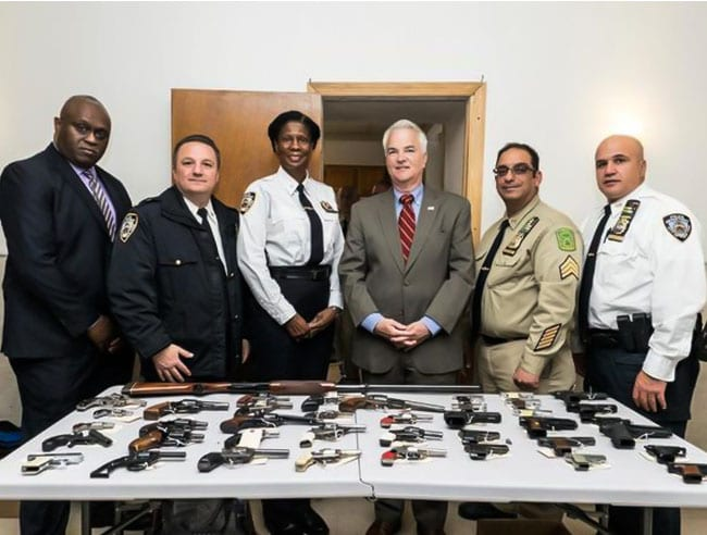 DA McMahon, together with the NYPD, standing in front of a table with the gun buybacks