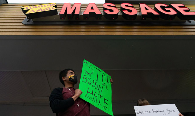 Jesus Estrella holds a sign of solidarity outside Youngs Asian Massage where four people were shot and killed on March 17, 2021 in Acworth, Georgia. Suspect Robert Aaron Long, 21, was arrested after a series of shootings Tuesday night at three Atlanta-area spas left eight people dead, including six Asian women.