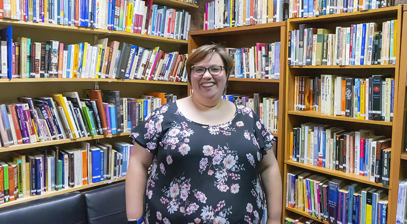 profile pic of Lisa Sloan with glasses and a floral dress in a library surrounded by books